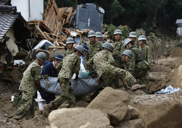 Japan Self-Defense Force (JSDF) soldiers and police officers carry the body of a victim in a plastic bag at a site where a landslide swept through a residential area at Asaminami ward in Hiroshima, western Japan, August 20, 2014. (Photo by Toru Hanai/Reuters)