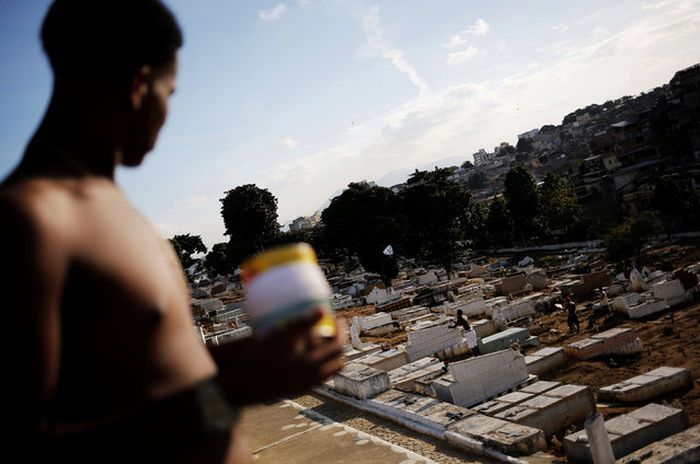 People fly kites in a cemetery in the Vila Operaria Favela of Rio de Janeiro, Brazil, June 26, 2016. (Photo by Nacho Doce/Reuters)