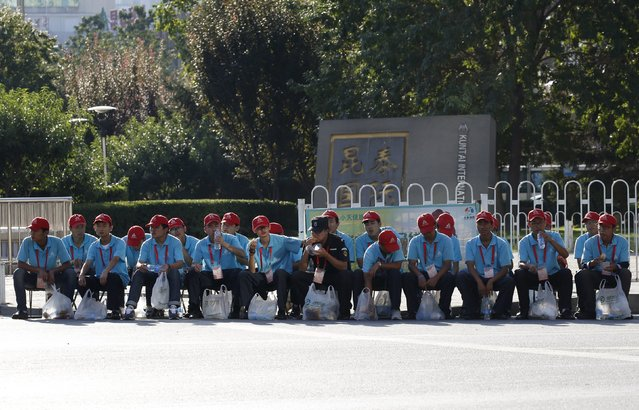 Security volunteers sit on the roadside, ahead of the military parade to mark the 70th anniversary of the end of World War Two, in Beijing, China, September 3, 2015. (Photo by Kim Kyung-Hoon/Reuters)