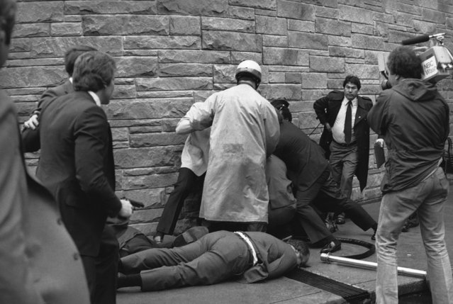 Secret Service agent Timothy J. McCarthy, foreground, Washington policeman, Thomas K. Delehanty, center, and presidential Press Secretary, James Brady, background, lie wounded on a street outside a Washington hotel after shots were fired at U.S. President Reagan on March 30, 1981. McCarthy threw himself into the line of fire and Delehanty, on crowd control duty, was standing close to the gunman, John Warnock Hinckley, Jr., who pushed a pistol through a cluster of bystanders and fired six shots. Police and secret service subdue the gunman in the background. (Photo by Ron Edmonds/AP Photo)