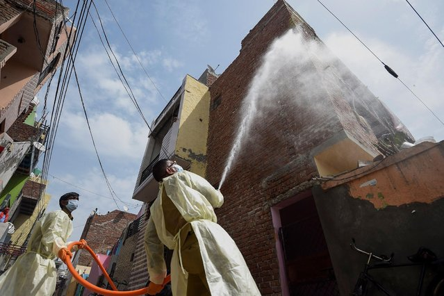Municipal workers spray disinfectant solution to sanitise a residential area during a government-imposed nationwide lockdown as a preventive measure against the spread of the COVID-19 coronavirus in Faridabad on April 15, 2020. (Photo by Money Sharma/AFP Photo)