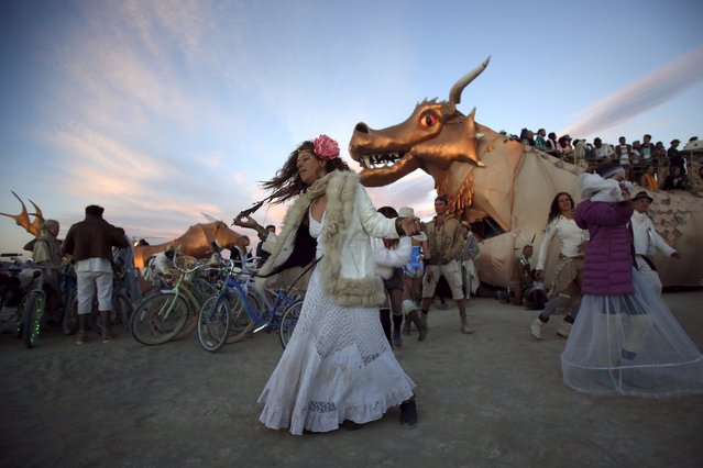 "Deby Dai dances before sunrise during the Burning Man 2015 ""Carnival of Mirrors"" arts and music festival in the Black Rock Desert of Nevada, September 3, 2015. (Photo by Jim Urquhart/Reuters)"