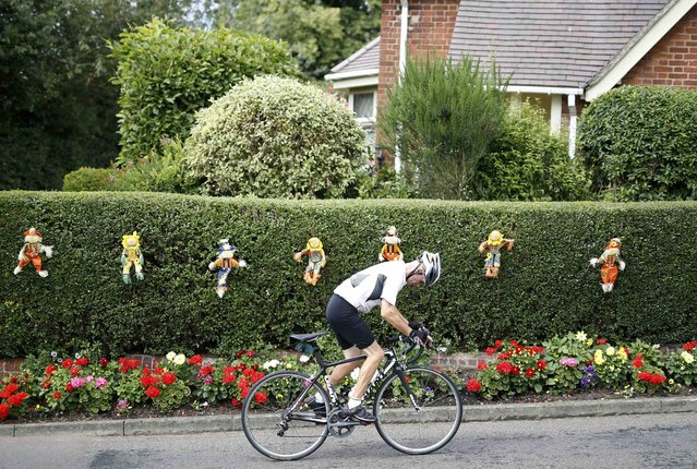 A man cycles past scarecrows during the Scarecrow Festival in Heather, Britain July 31, 2016. (Photo by Darren Staples/Reuters)