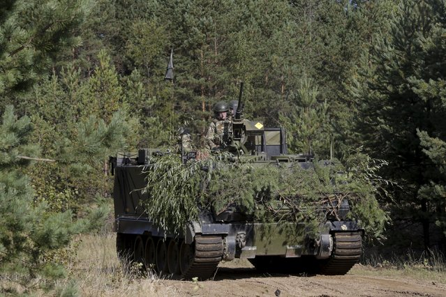 "Danish troops with M113 armored personnel carrier take part in a live fire exercise in a tactical environment ahead of the ""Silver Arrow"" drill in Adazi training field, Latvia,  September 5, 2015. (Photo by Ints Kalnins/Reuters)"