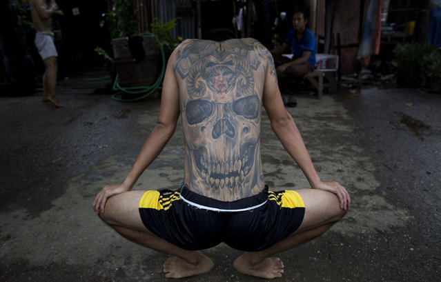 In this Tuesday, July 14, 2015, photo, Phoe Thaw, center, a member of the White New Blood lethwei fighters club, a Myanmar traditional martial-arts club which practices a rough form of kickboxing, stretches during a practice session in their gym on a street in Oakalarpa, north of Yangon, Myanmar. (Photo by Gemunu Amarasinghe/AP Photo)