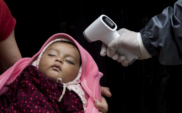 A Nepali health worker checks the body temperature of a child during a national vaccination campaign at Ramghaat primary health center in Kathmandu, Nepal, 22 April 2020. In spite of the nationwide lockdown, Nepal's government carried out a free national vaccination campaign providing B.C.G. Polio, Japanese Encephalitis and Measles vaccine for children under two years of age. Nepal has been under a nationwide lockdown since 24 March 2020 in a bid to quell the spread of coronavirus. (Photo by Narendra Shrestha/EPA/EFE)