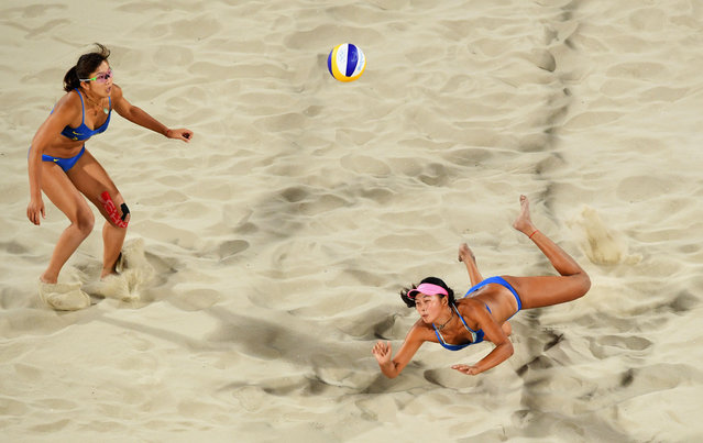 Fan Wang of China dives for the ball as team mate Yuan Yue of China looks on during the Women's Beach Volleyball preliminary round Pool C match against Isabelle Forrer (1) and Anouk Verge-Depre of Switzerland  on Day 1 of the Rio 2016 Olympic Games at the Beach Volleyball Arena on August 6, 2016 in Rio de Janeiro, Brazil. (Photo by Quinn Rooney/Getty Images)
