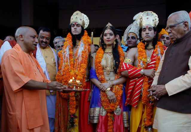 Yogi Adityanath (L), Chief Minister of India's most populous state of Uttar Pradesh, worships artists dressed as Rama, his wife Sita and his brother Laxman during Diwali, the Hindu festival of lights, celebrations in Ayodhya, India, October 18, 2017. (Photo by Pawan Kumar/Reuters)