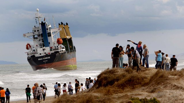A cargo ship sits near shore after running aground during a heavy storm at Saler beach near Valencia, on September 29, 2012. At least eight people, including a young girl and an elderly woman, have died in Spain as a result of floods brought on by downpours, regional officials said. (Photo by Alberto Saiz/Associated Press)