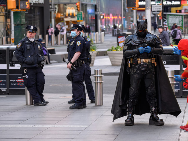 NYPD officers and Batman stand in Times Square during the coronavirus pandemic on May 20, 2020 in New York City. COVID-19 has spread to most countries around the world, claiming over 329,000 lives with over 5 million infections reported. (Photo by Noam Galai/Getty Images)