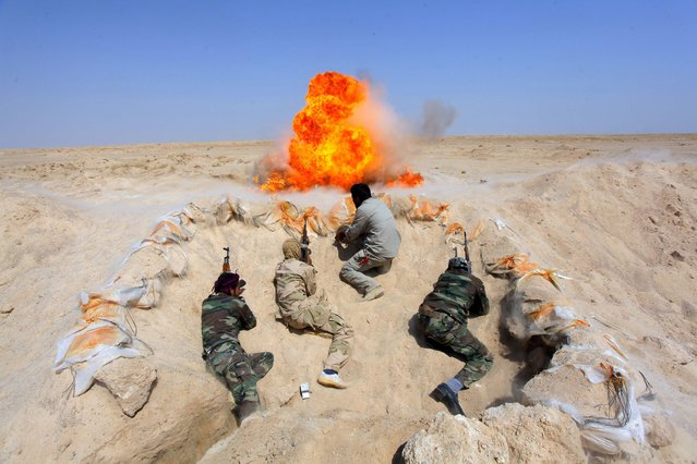 Shi'ite fighters, who have joined the Iraqi army to fight against militants of the Islamic State, formerly known as the Islamic State of Iraq and the Levant (ISIL), take part in field training in the desert in the province of Najaf, September 16, 2014. (Photo by Alaa Al-Marjani/Reuters)