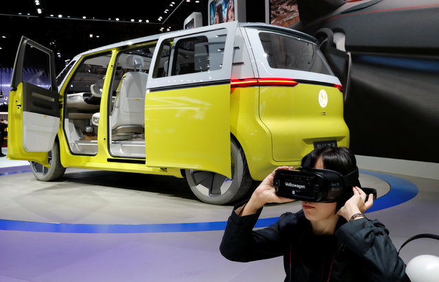 A visitor uses virtual reality device next to Volkswagen's concept I.D. Buzz during media preview of the 45th Tokyo Motor Show in Tokyo, Japan on October 25, 2017. (Photo by Kim Kyung-Hoon/Reuters)