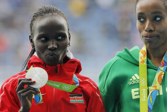 Silver medalist Vivian Jepkemoi Cheruiyot of Kenya and gold medalist Almaz Ayana (R) of Ethiopia during the medal ceremony for the women's 10000m final of the Rio 2016 Olympic Games Athletics, Track and Field events at the Olympic Stadium in Rio de Janeiro, Brazil, 12 August 2016. (Photo by Sergei Ilnitsky/EPA)