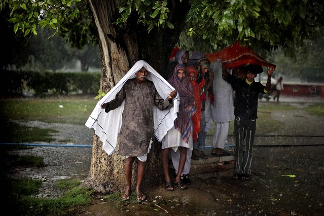 Men take shelter under a tree during a sudden downpour in New Delhi, India October 23, 2012. (Photo by Altaf Qadri/Associated Press)