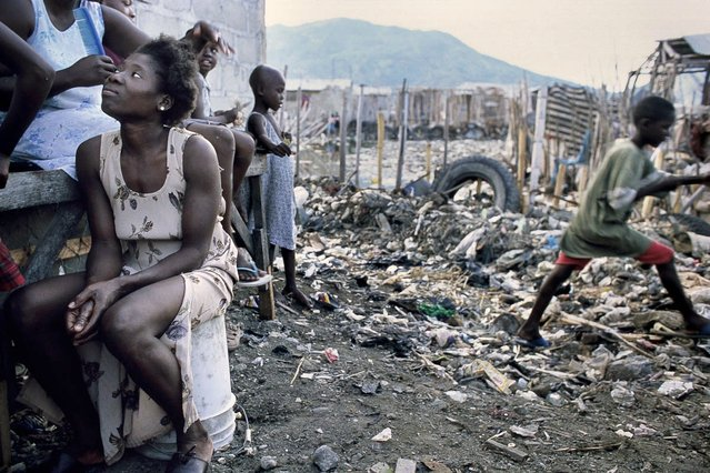 Cap-Haitien, Haiti. In Bas-Aviation slums, located at the end of the airport runways, a woman is having her hair done in October 2003. (Photo by Jean-Claude Coutausse)