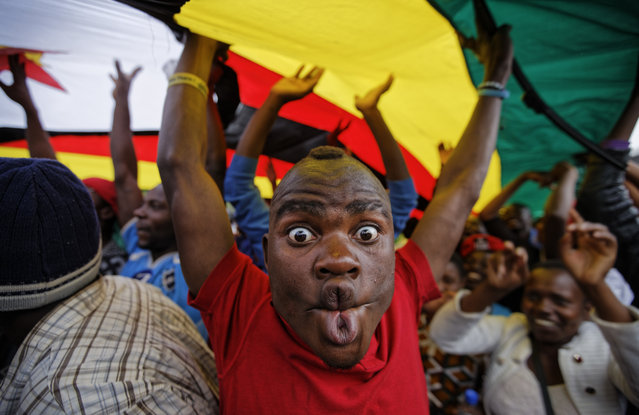 A happy protester pulls a face as he and others stand under a large national flag, at a demonstration of tens of thousands at Zimbabwe Grounds in Harare, Zimbabwe Saturday, November 18, 2017. Opponents of Mugabe are demonstrating for the ouster of the 93-year-old leader who is virtually powerless and deserted by most of his allies. (Photo by Ben Curtis/AP Photo)