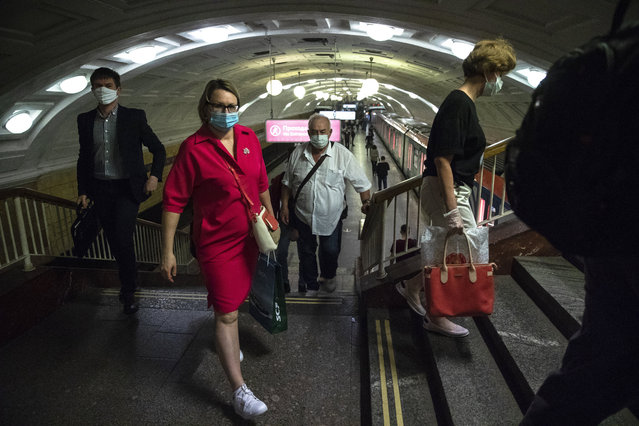 People wearing face masks to protect against coronavirus walk through the subway in Moscow, Russia, Wednesday, June 10, 2020. Moscow residents are no longer required to stay at home or obtain electronic passes for traveling around the city. All restrictions on taking walks, using public transportation or driving have been lifted as well. (Photo by Pavel Golovkin/AP Photo)