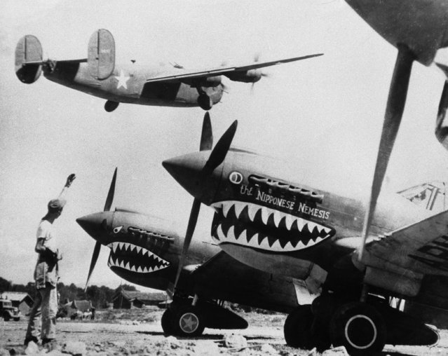 A U.S. Army B-24 Liberator Bomber is hailed by a ground crewman as it takes off over a line of shark- nosed fighter planes at an advanced base in China on a mission on October 10, 1943, to bomb Japanese installations. (Photo by AP Photo)