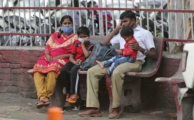 Indians wearing masks wait for transport outside a hospital in Jammu, India, Tuesday, June 23, 2020. India has been recording about 15,000 new infections each day, and some states Tuesday were considering fresh lockdown measures to try to halt the spread of the virus in the nation of more than 1.3 billion. (Photo by Channi Anand/AP Photo)