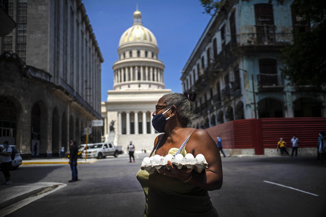 A woman wearing a face mask as a precaution amid the spread of the new coronavirus carries eggs past the Capitol building in Havana, Cuba, Tuesday, June 16, 2020. (Photo by Ramon Espinosa/AP Photo)