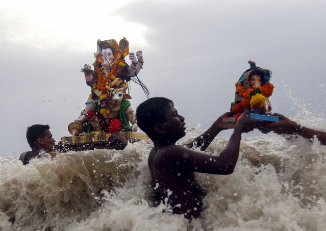 Devotees carry idols of the Hindu god Ganesh, the deity of prosperity, into the Arabian Sea on the fifth day of the ten-day-long Ganesh Chaturthi festival in Mumbai, India, September 21, 2015. (Photo by Danish Siddiqui/Reuters)