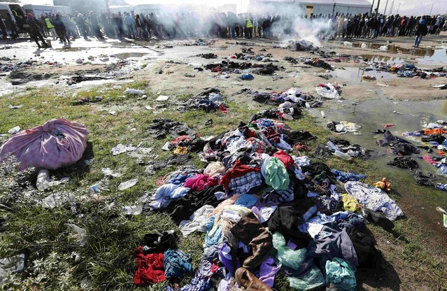 "Discarded clothes and personal belongings are scattered on the ground as migrants queue during food distribution at the makeshift camp called ""The New Jungle"" in Calais, France, September 19, 2015. (Photo by Regis Duvignau/Reuters)"