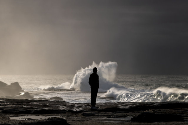 A sightseer checks out the large swell impacting the coast at Clovelly Beach on July 16, 2020 in Sydney, Australia. The Bureau of Meteorology has issued a severe weather warning for Sydney and large parts of coastal NSW, with damaging winds and surf expected across the state. (Photo by Brook Mitchell/Getty Images)
