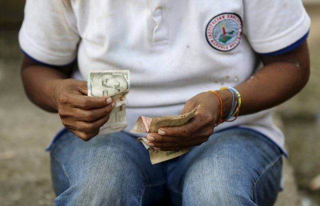A Colombian Nukak Maku Indian woman counts money at a park in San Jose del Guaviare of Guaviare province September 4, 2015. (Photo by John Vizcaino/Reuters)
