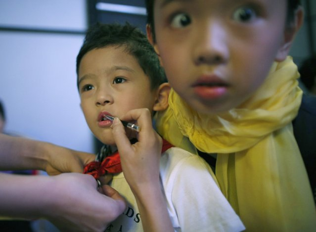 A child model looks at the camera while another has make-up applied at the backstage during a rehearsal for the Dong Wenmei T100 Children's Collection during China Fashion Week in Beijing October 29, 2014. (Photo by Kim Kyung-Hoon/Reuters)