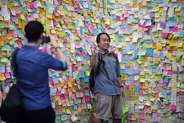 A man gestures as he has his picture taken in front of a wall with messages of support for the pro-democracy movement, in part of Hong Kong's financial central district occupied by protesters October 29, 2014. (Photo by Damir Sagolj/Reuters)