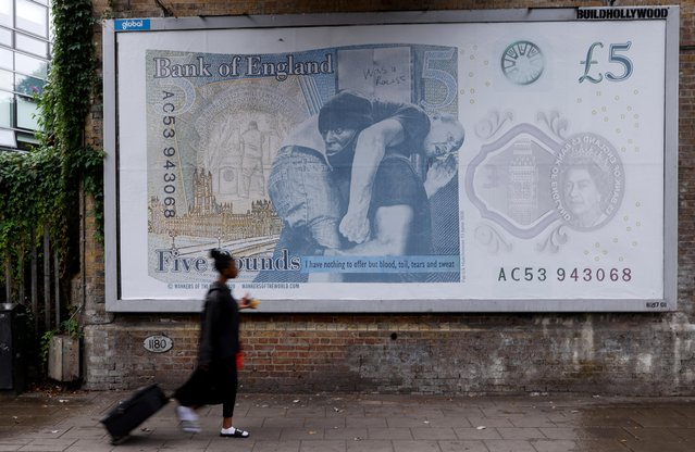 """A passerby walks past a billboard depicting the artwork """"Churchill Fiver Reboot"""" by the """"Wankersoftheworld.com"""" art collective, in Peckham, South London, Britain, August 18, 2020. (Photo by John Sibley/Reuters)"""