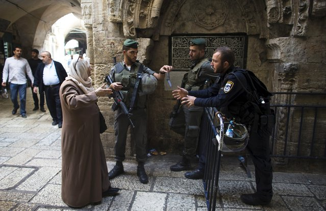 An Israeli border policeman checks the identity card of a Palestinian woman as she makes her way to Al-Aqsa mosque, on a compound known by Muslims as the Noble Sanctuary and by Jews as the Temple Mount, in Jerusalem's Old City October 8, 2015. (Photo by Ronen Zvulun/Reuters)