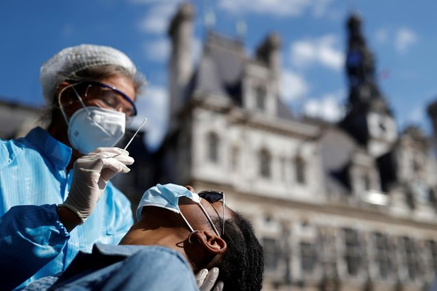 A health worker, wearing a protective suit and a face mask, prepares to administer a nasal swab to a patient at a testing site for the coronavirus disease (COVID-19) installed in front of the city hall in Paris, France, September 2, 2020. (Photo by Christian Hartmann/Reuters)