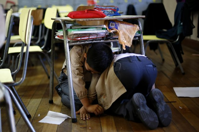 Children take cover under their desk inside a school during an earthquake drill in Santiago, November 13, 2014. (Photo by Ivan Alvarado/Reuters)