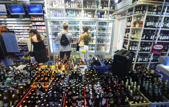 """Tourists buy drinks at a store on Schoenhauser Allee street in Berlin, Germany, August 27, 2016. For many Berlin clubbers nights can be long and expensive. So-called """"Spaeties"""" (late night convenience stores) sell alcohol for cheaper prices than are found in most club. (Photo by Hannibal Hanschke/Reuters)"""