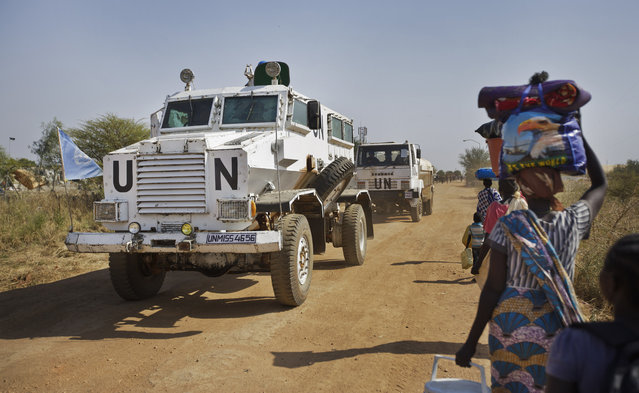 In this Monday, December 30, 2013 file photo, a United Nations armored vehicle passes displaced people walking towards the U.N. Protection of Civilians camp in Malakal, South Sudan. The United Nations peacekeeping mission in South Sudan said on Friday, Sept. 4, 2020 that it has begun withdrawing its troops and police from the protection of civilians camps that continue to shelter more than 180,000 people two years after the end of the country's civil war. (Photo by Ben Curtis/AP Photo/File)
