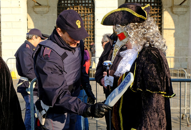 A masked reveller is controlled by an Italian Policeman during the Venice Carnival, Italy, February 4, 2018. (Photo by Manuel Silvestri/Reuters)