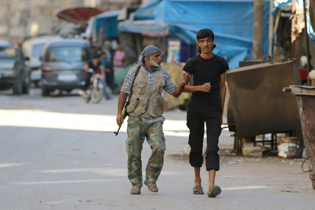 Rebel fighters walk inside a market in the rebel-held al-Shaar neighbourhood of Aleppo, Syria, September 17, 2016. (Photo by Abdalrhman Ismail/Reuters)