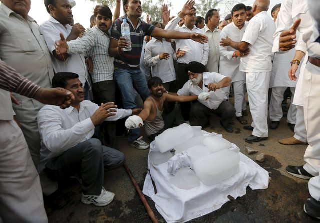 The father (bottom C) of two children who were burnt alive, with his hands bandaged, wails next to the bodies of his children wrapped in white shrouds, as he along with other villagers block a national highway during a protest against the crime at Ballabhgarh in the northern state of Haryana, India, October 21, 2015. (Photo by Adnan Abidi/Reuters)