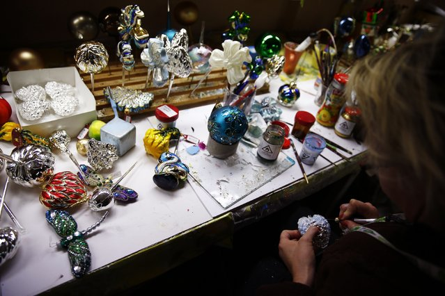 A worker paints Christmas decorations on glass baubles at the Silverado manufacture of hand-blown Christmas ornaments in the town of Jozefow, outside Warsaw December 2, 2014. (Photo by Kacper Pempel/Reuters)