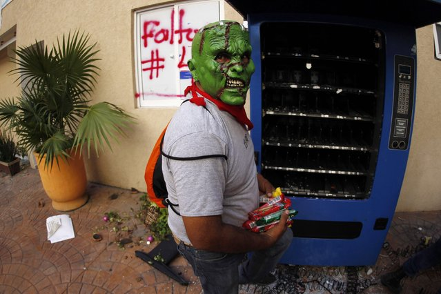 A masked CETEG (State Coordinator of Teachers of Guerrero) member loots a vending machine during a protest demanding the government find of missing students of the Ayotzinapa Teacher Training College Raul Isidro Burgos, at the General Attorney building in Chilpancingo, in the southern Mexican state of Guerrero December 1, 2014. (Photo by Jorge Dan Lopez/Reuters)