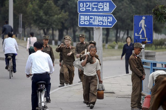 """""""Soldier-builders"""" carry things in central Pyongyang October 8, 2015. (Photo by Damir Sagolj/Reuters)"""