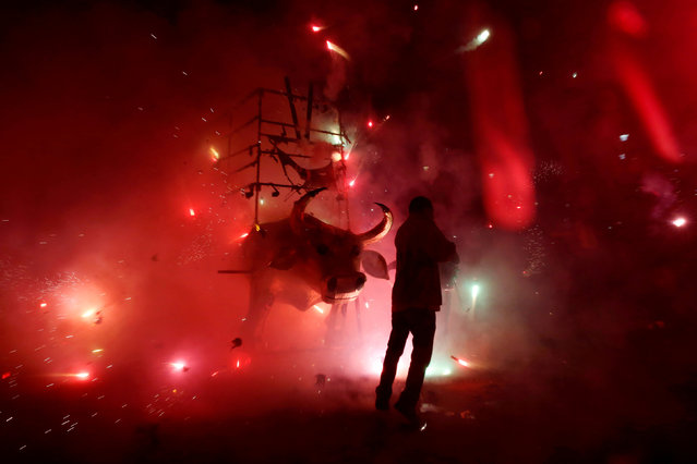 """A man enjoys the fireworks exploding from a traditional bull figure known as """"El Torito"""" during the annual San Juan de Dios celebrations in Tultepec, on the outskirts of Mexico City, Mexico March 8, 2018. (Photo by Carlos Jasso/Reuters)"""