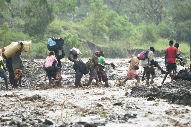 Haitian people cross the river La Digue in Petit Goave where the bridge collapsed during the rains of the Hurricane Matthew, southwest of Port-au-Prince, October 5, 2016. (Photo by Hector Retamal/AFP Photo)
