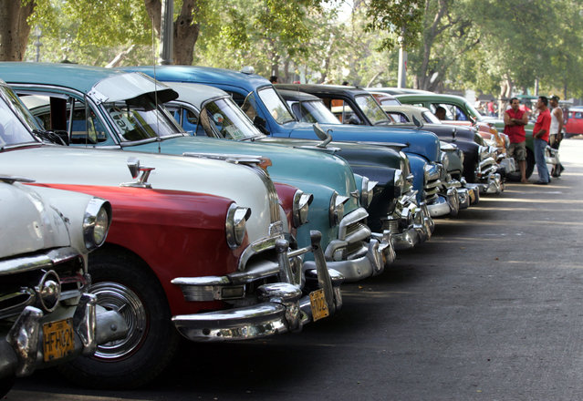 Vintage cars used as taxis are lined up in downtown Havana, May 4, 2006. (Photo by Claudia Daut/Reuters)