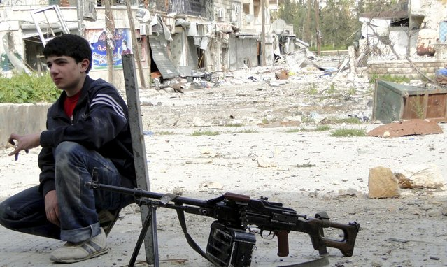 A boy sits near a weapon in Aleppo's Salaheddine district March 28, 2013. Picture taken March 28, 2013. (Photo by Mahmoud Hassano/Reuters)