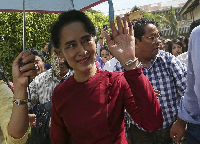 Myanmar pro-democracy leader Aung San Suu Kyi waves at supporters as she visits polling stations at her constituency Kawhmu township November 8, 2015. (Photo by Soe Zeya Tun/Reuters)