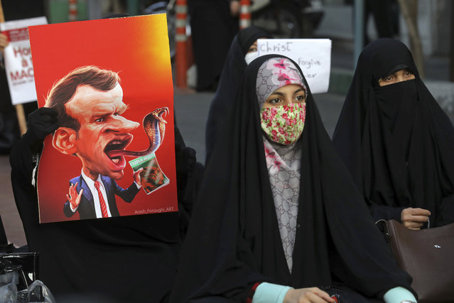 Iranian protesters hold defaced pictures of French President Emmanuel Macron during a protest against Macron and the publishing of caricatures of the Prophet Muhammad they deem blasphemous, in front of French Embassy in Tehran, Iran, Wednesday, October 28, 2020. Macron has vowed his country will not back down from its secular ideals and defense of free speech. (Photo by Ebrahim Noroozi/AP Photo)