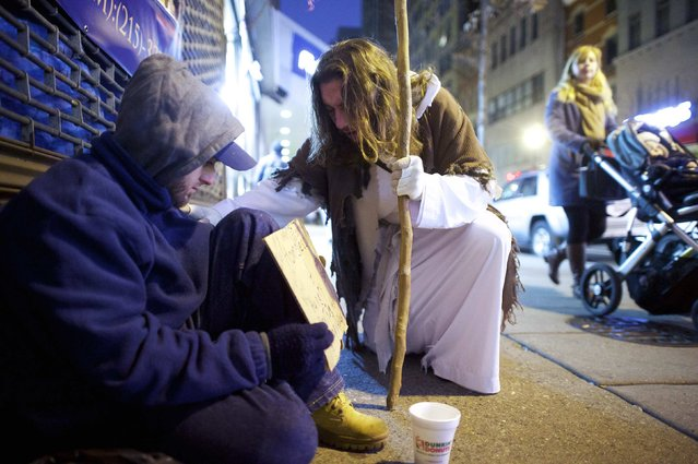"Michael Grant, 28, ""Philly Jesus"", prays with a beggar in Philadelphia, Pennsylvania December 14, 2014. (Photo by Mark Makela/Reuters)"