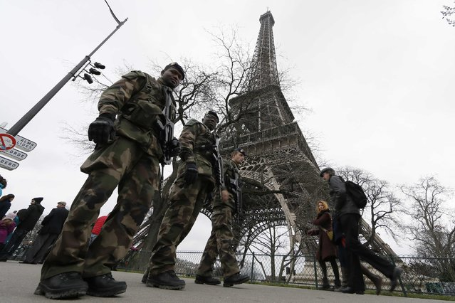 "French soldiers patrol near the Eiffel Tower in Paris as part of the ""Vigipirate"" security plan December 23, 2014. French security forces stepped up protection of public places on Tuesday after three acts of violence in three days left some 30 wounded and reignited fears about France's vulnerability to attacks by Islamic radicals. (Photo by Gonzalo Fuentes/Reuters)"